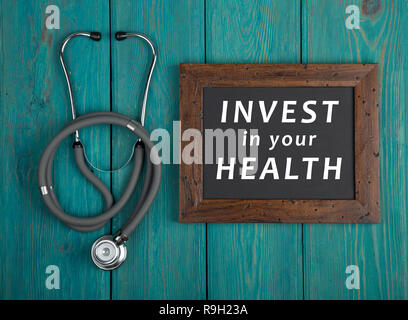 Medecine concept - Blackboard with text 'Invest in your health' and stethoscope on blue wooden background - Stock Photo