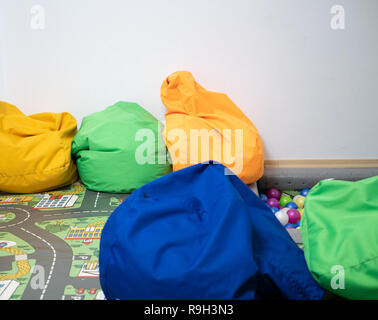 lot of vivid vibrant bean bags at kids playground zone at kindergarten, indoor image with lot of copy space on white background wall - Stock Photo