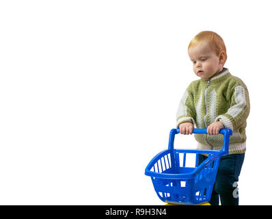 adorable little 2 year white caucasian boy shopping at kids store. walking with plastic shopping cart. wide image cutout isolated on white background - Stock Photo