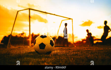 Silhouette action sport outdoors of a group of kids having fun playing soccer football on green grass field for exercise. - Stock Photo