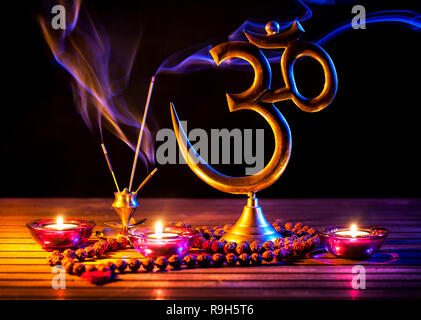 Om symbol, incense smoke, candle and japa mala on wooden table at black background - Stock Photo