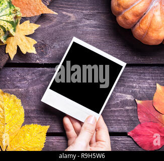 Hand holding retro photo near autumn leaves and pumpkin on wooden background - Stock Photo