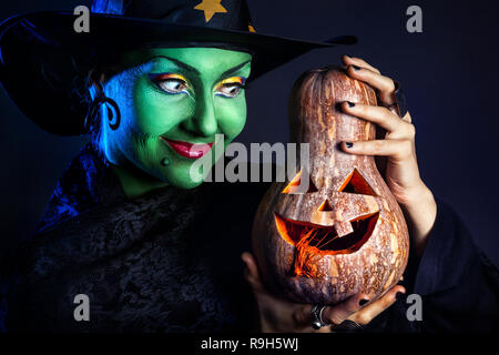 Witch with green skin holding carved Halloween pumpkin at dark background - Stock Photo