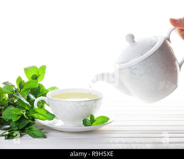 Mint tea pouring out from teapot in the cup near mint leaves at white background - Stock Photo