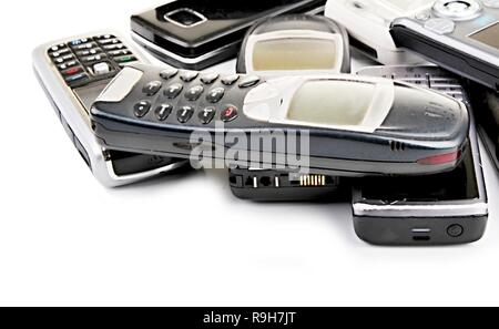 old mobile phones piled up on a table with white background no people stock photo - Stock Photo