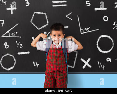 Young boy in school uniform flexing his muscles infront of blackboard. - Stock Photo
