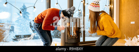 Young couple dressed in bright sweaters looking at the fire place in the modern house in the mountains during the winter time - Stock Photo