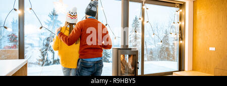 Young couple dressed in bright sweaters enjoying landscape view on the mountains standing together in the modern house during winter time - Stock Photo