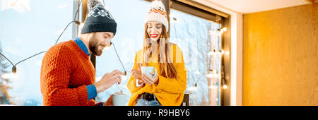 Young couple dressed in bright sweaters and hats standing together with hot drinks near the fireplace in the modern house durnig winter time - Stock Photo