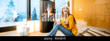 Portrait of a young woman in sweater and hat sitting with hot drink near the fireplace in the modern house in the mountains - Stock Photo