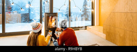 Young couple dressed in bright sweaters sitting near the fireplace in the modern house in the mountains durnig winter time - Stock Photo