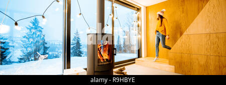 Couple standing outdoors on the terrace of the house with fireplace during the winter time. Interior view through the window - Stock Photo