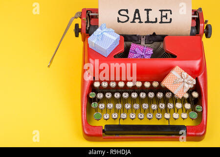 Holidays concept - red typewriter with craft paper with text 'Sale', gift boxes on yellow background - Stock Photo