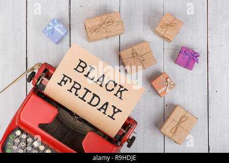 Sale concept - red typewriter with craft paper with text 'Black friday', gift boxes on white wooden background - Stock Photo