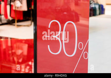 Sale. Shop window with 30 percent discount. Winter sale. Window shop with dressed mannequin, text Sale and 30 percent discount.Seasonal discounts in the store.New Year discounts.The final sale at a clothing boutique. - Stock Photo
