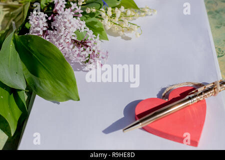 Mock up letter about love.Red wooden heart lies on blank white paper on a wooden table with spring flowers, a greeting card for Valentine's Day with a place for your text. Flat lay, lilac and lilies of the valley. design to Valentine's Day - Stock Photo