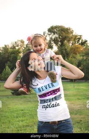 stylish young mum and her cute daughter have a lot fun time together. Mother is piggybacking her very sweet daughter - Stock Photo