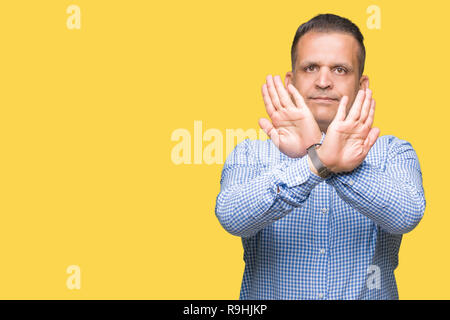 Middle age arab business man over isolated background Rejection expression crossing arms and palms doing negative sign, angry face - Stock Photo