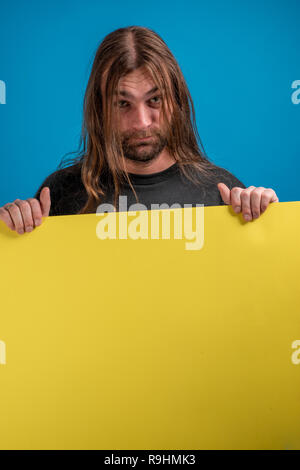 Portrait of male displaying a serious face while holding a yellow banner. Studio shot against blue background - Stock Photo