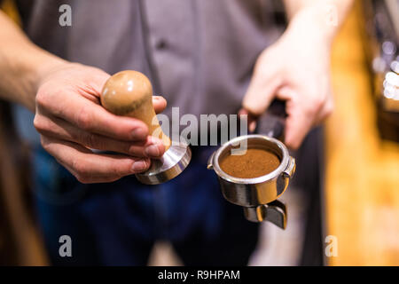 Man is using a tamper to press freshly ground morning coffee into a coffee tablet - Stock Photo