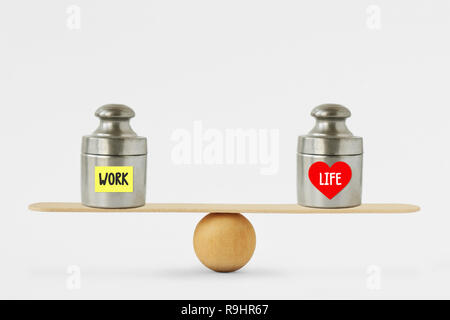 Weights with the words Work and Life written on paper note on balance scale - Concept of balance between work and life - Stock Photo