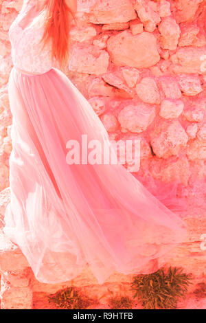 The bride in a pink wedding dress on the background of stones in nature. The concept of fashion colors 2019, living coral - Stock Photo