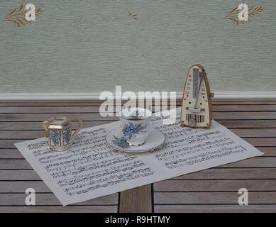 English teacup and saucer, cream jug, with floral decor, and metronome for music on a sheet of music - Stock Photo