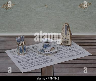 English teacup and saucer, spoon vase and teaspoon, with floral decor, and metronome for music on a sheet of music - Stock Photo