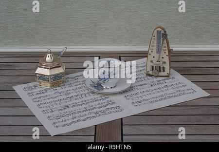 English teacup and saucer, sugar bowl and sugarspoon, with floral decor, and metronome for music on a sheet of music - Stock Photo