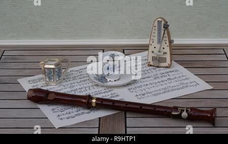 English teacup and saucer, cream jug, with floral decor, metronome for music and a block flute on a sheet of music - Stock Photo