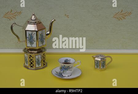 English teacup, saucer, silver-plated teapot on a silver stove, and cream jug, with floral decor - Stock Photo