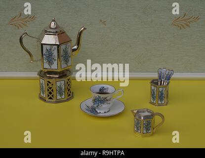 English teacup, saucer, silver-plated teapot on a silver stove, spoon vase with teaspoon and cream jug, with floral decor - Stock Photo
