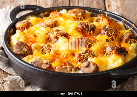 Main course from Cheese Potatoand Smoked Sausage Casserole closeup on the pan on the table. horizontal - Stock Photo