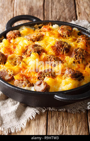 Delicious potato casserole, sausages with cheese sauce close-up in a frying pan on the table. vertical - Stock Photo
