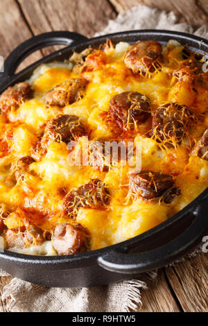 Jolean's Cheese Potatoand Smoked Sausage Casserole closeup on the pan on the table. vertical - Stock Photo