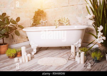 Beautiful bathroom with bath, flowers and candles at home. Bright interiors, the romance of the concept - Stock Photo