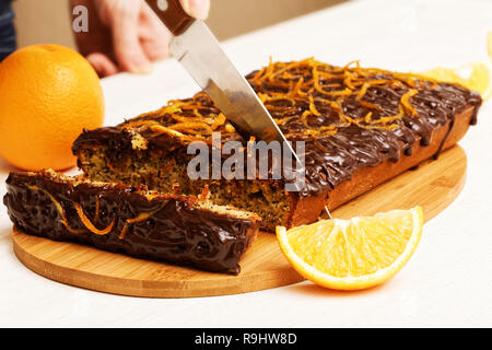 Housewife cut off piece of chocolate and orange cake - Stock Photo