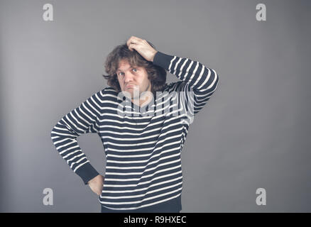 Puzzled guy with messy hair, frowning and looking unsatisfied scratching head, thinking deeply about something on grey wall background. Human facial e - Stock Photo