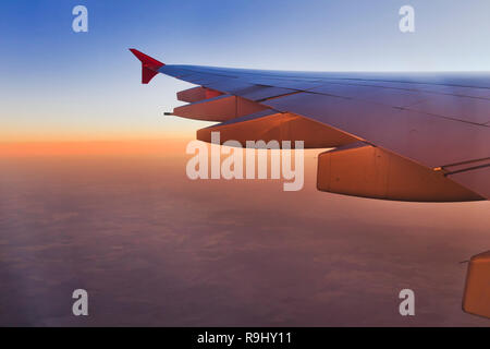 Soft smoth pink sunlight of rising sun over distant horizon under wing of modern passenger airplane high in the sky over flat land seen from window. - Stock Photo