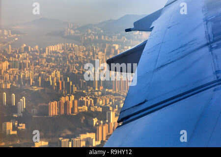 Mid-air view down on over developed islands of Hong Kong with airplane wing in a sight seen out of passenger window. - Stock Photo
