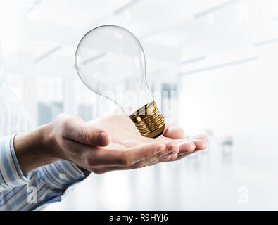 Concept of idea or energy as light bulb in male palms. Mixed med - Stock Photo