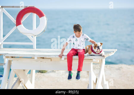 Handsome boy teen happyly spending time together with his friend bulldog on sea side Kid dog holding playing two sea stars close to life buoy float we - Stock Photo