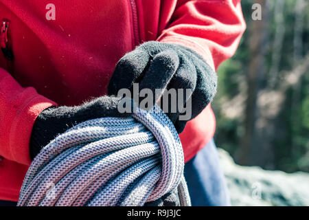 Close-up of a coiled blue climbing rope in the hands of a climber male - Stock Photo