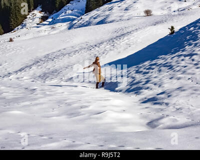 Fashion winter woman walking in the snow of the alps. - Stock Photo