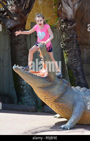 Young Girl Stands on a mouth of a Crocodile. Crocodiles account for less than one death per year in Australia. - Stock Photo