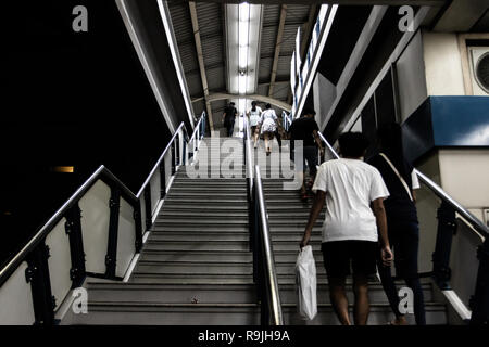 a few people walking up stair of a skytrain station in Bangkok, Thailand during the early night - Stock Photo