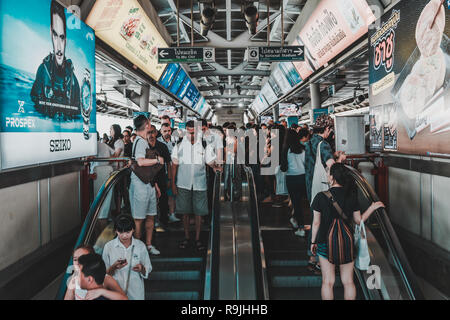 Commuters using the escalator to reach the platform floor of Siam BTS Skytrain Station in the middle of the day on weekend with direction sign overhea - Stock Photo