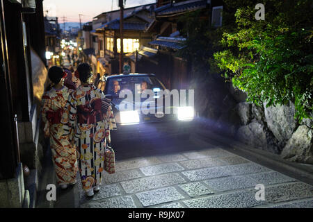 Japanese women in traditional clothes walking on Kyoto streets, Japan - Stock Photo