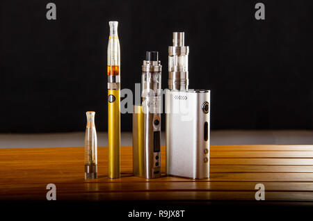 Popular vaping e cig devices mod.electronic cigarette over wooden background. vaporizer e-cig old device model. - Stock Photo