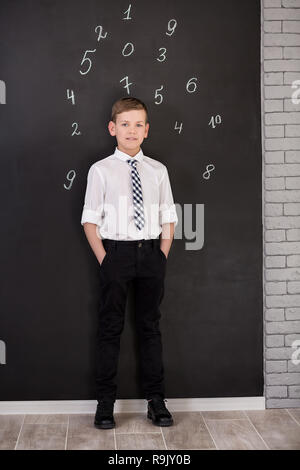 Handsome school boy in googles white shirt tie standing close to school desk with numbers above around the head - Stock Photo